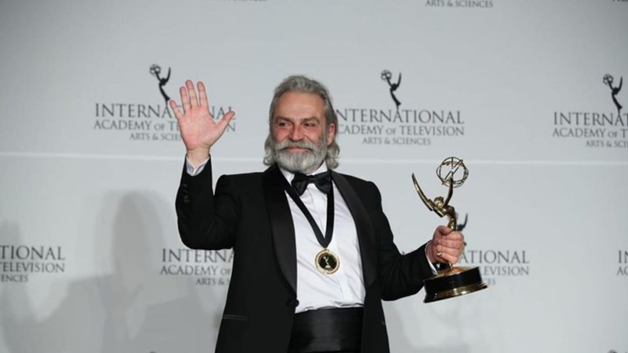 Elinde Grammy ödülünü tutan boynunda madalyası olan elini sallayan adam.