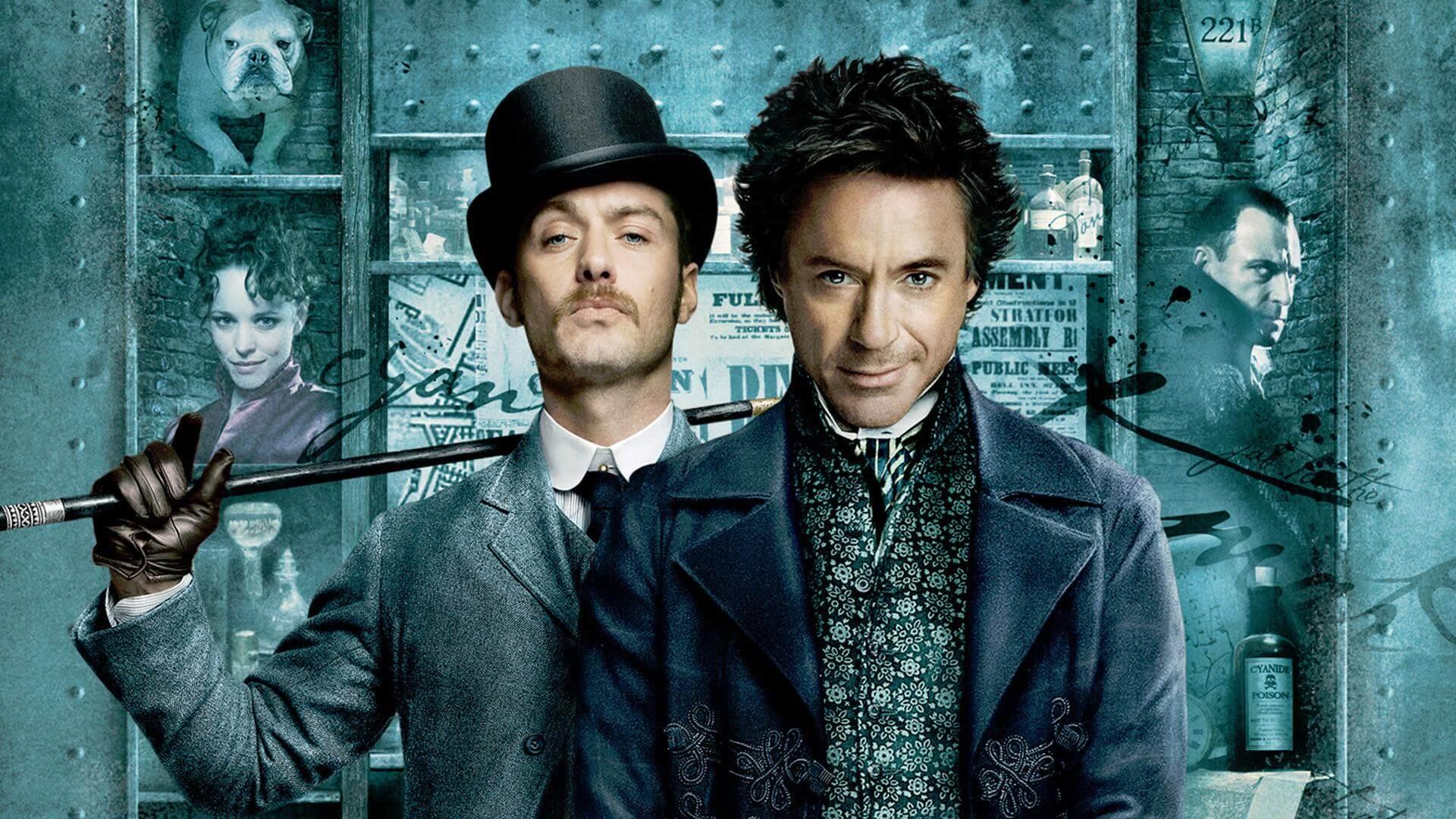 önde paltolu dağınıl saçlı bir adam, arkada şapkalı ve elinde baston bulunan bıyıklı gri paltolu bir adam.