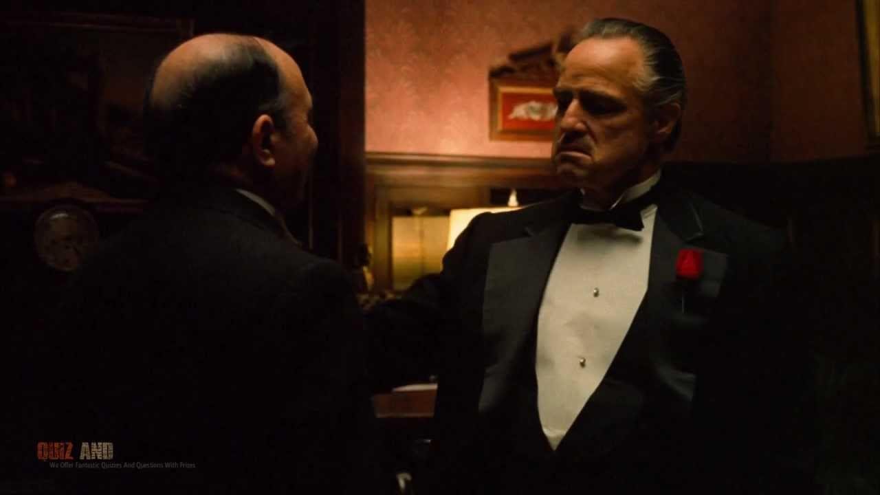 ceketinin cebinde gül bulunan takım elbiseli adam kel adamın kolunu tutuyor.