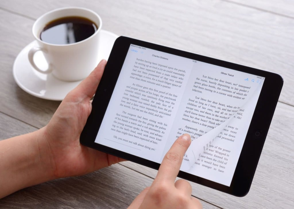 sol tarafında kahve, elindeki tabletinden elektronik kitap okuyan adam