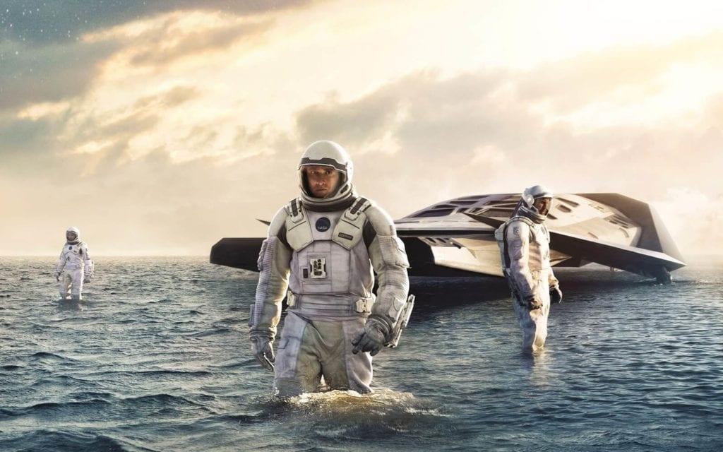 Suyun içinde üç kişi ve bir tane suyun üzerinde uzay aracı