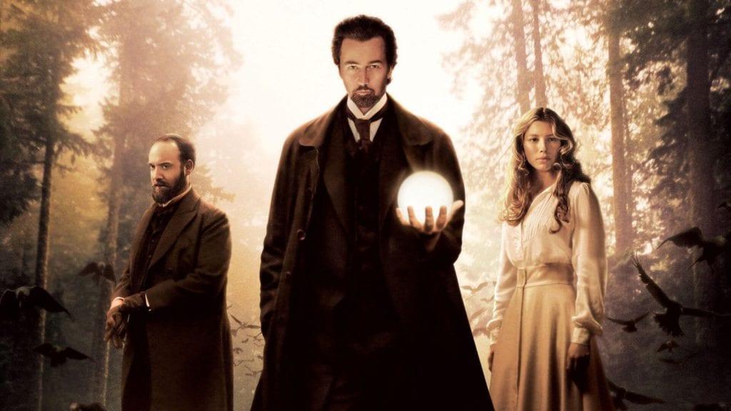 elinde küre olan bir adam solunda sakallı bir adam sağında sarışın bir kadın