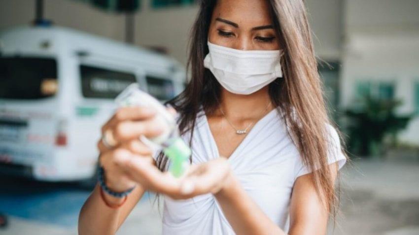 eline dezenfektan süren, yüzünde tıbbı maske olan bir kadın