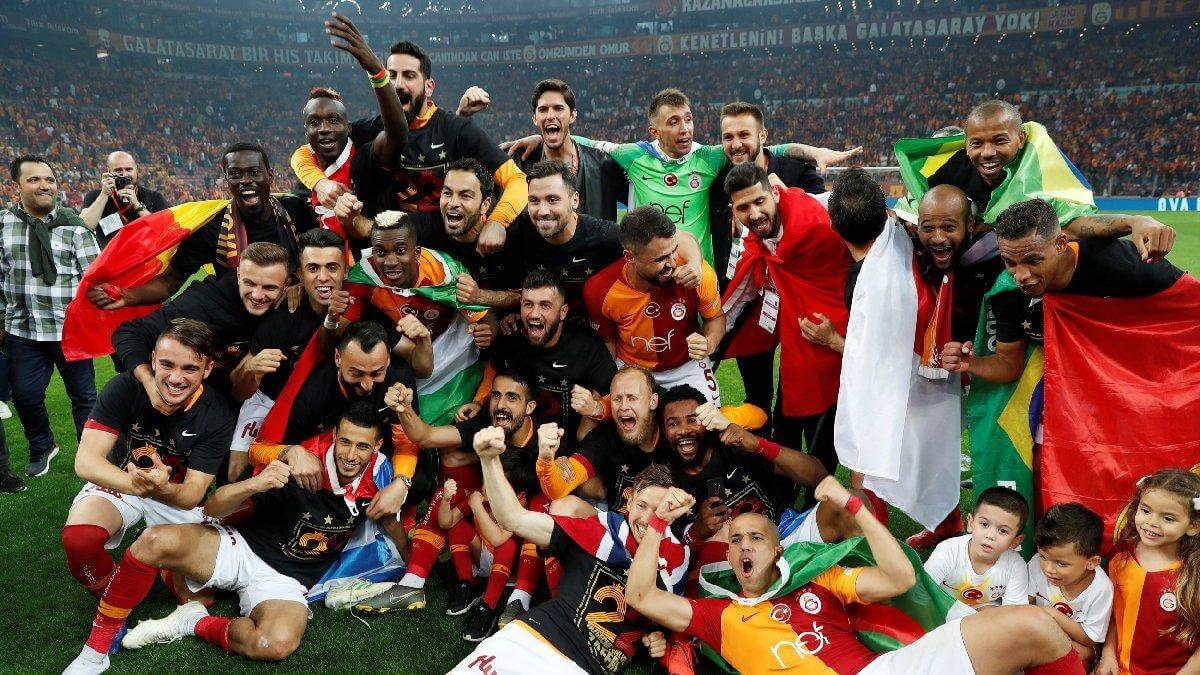 Sarı kırmızı formalı futbolcular kol kola girmiş fotoğraf çekiniyor.