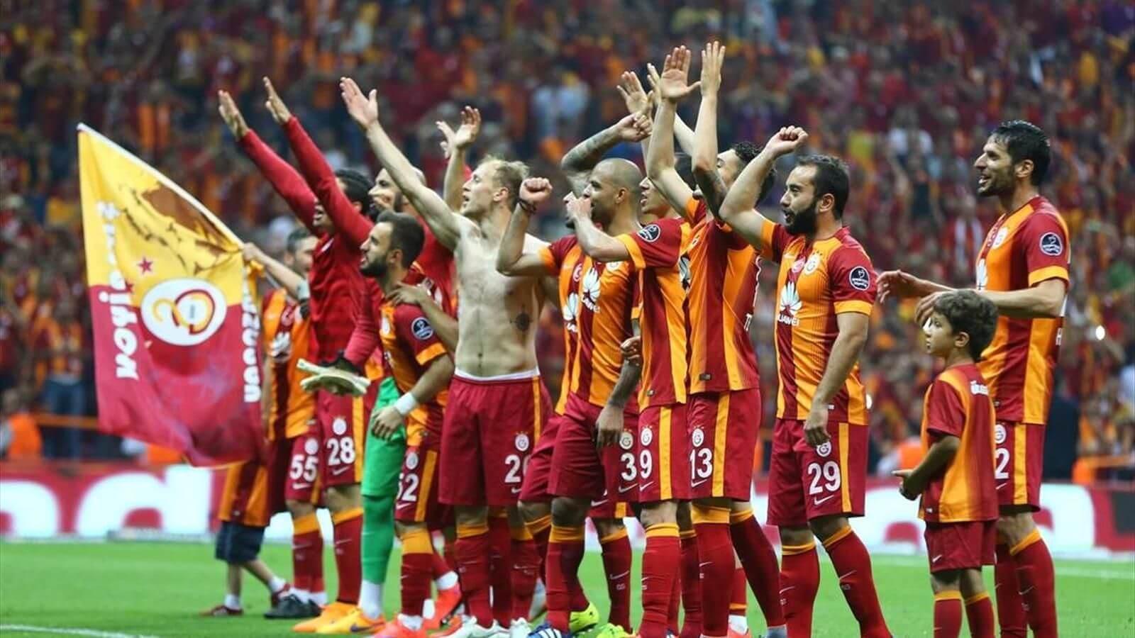 Sarı kırmızı formalı birçok futbolcu taraftara selam veriyor.