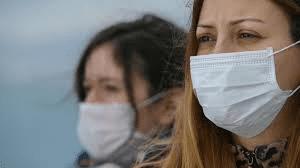 İki kız maske takmış bakıyor