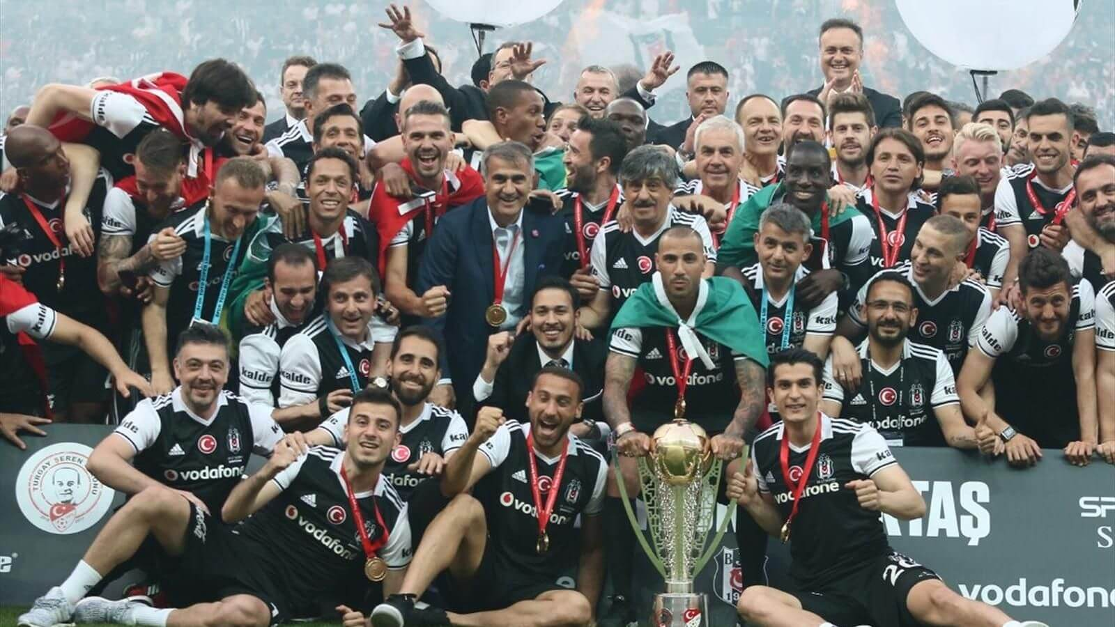 Siyah beyaz formalı futbolcular Süper lig kupası ile fotoğraf çekiniyor.