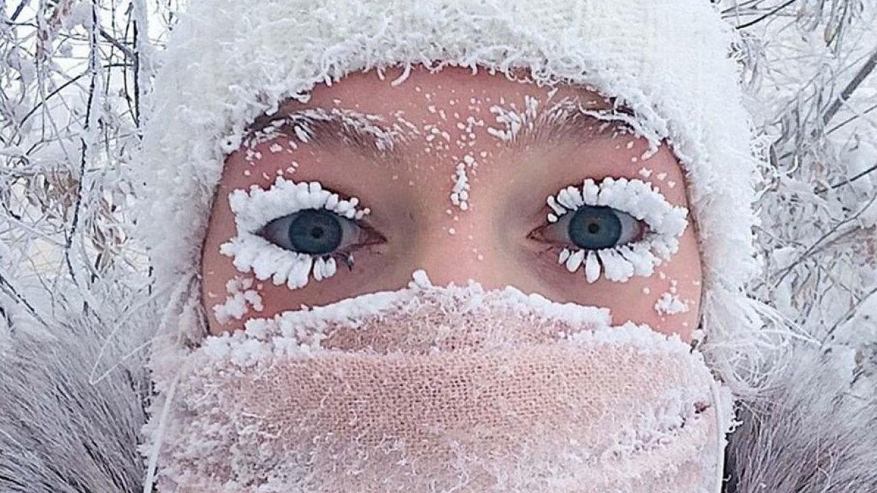 Mavi gözlü bir kız kirpikleri donmuş bir şekilde bakıyor.