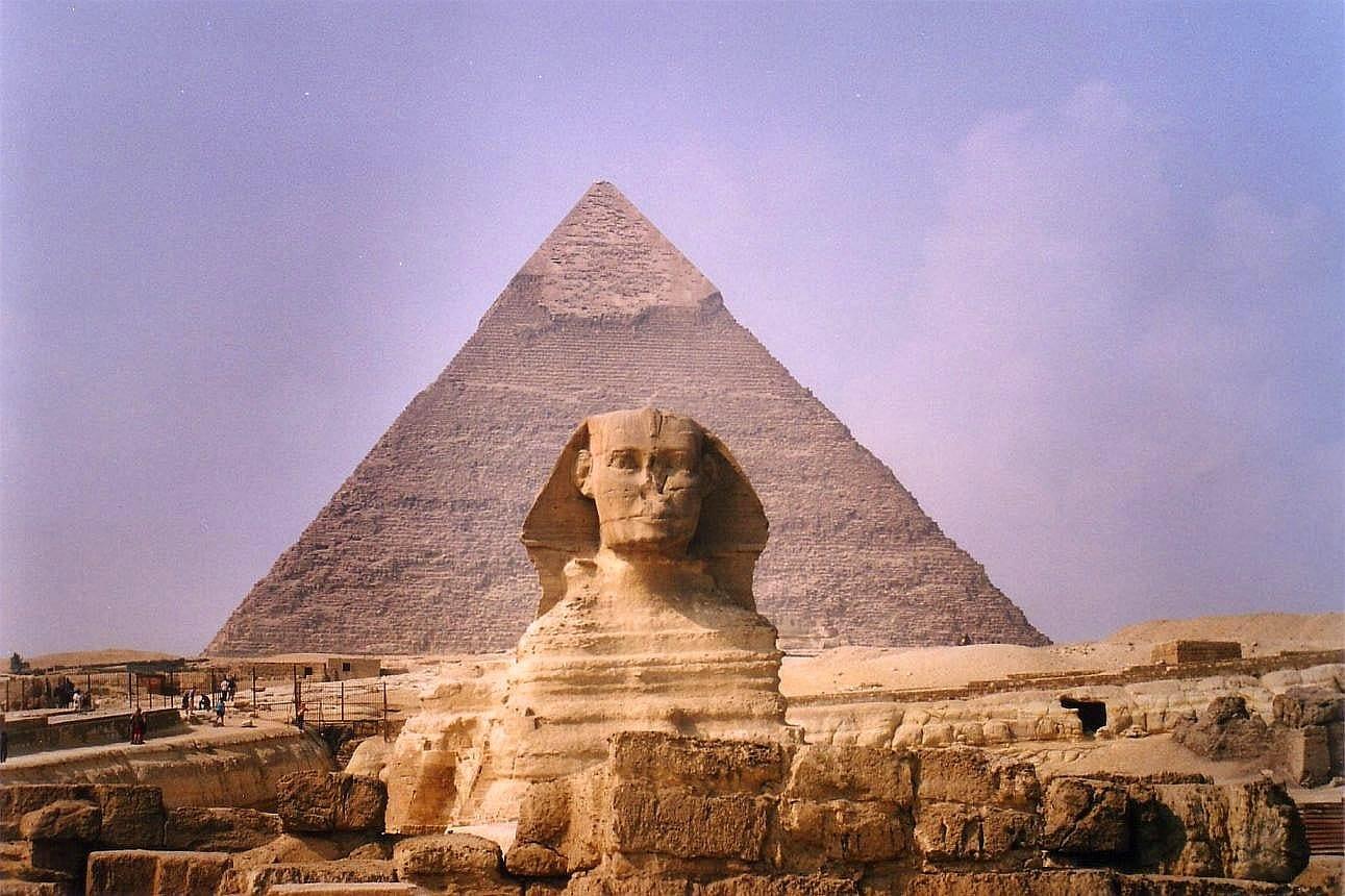 önde insana benzeyen bir heykel ve arkasında taştan yapılmış piramit