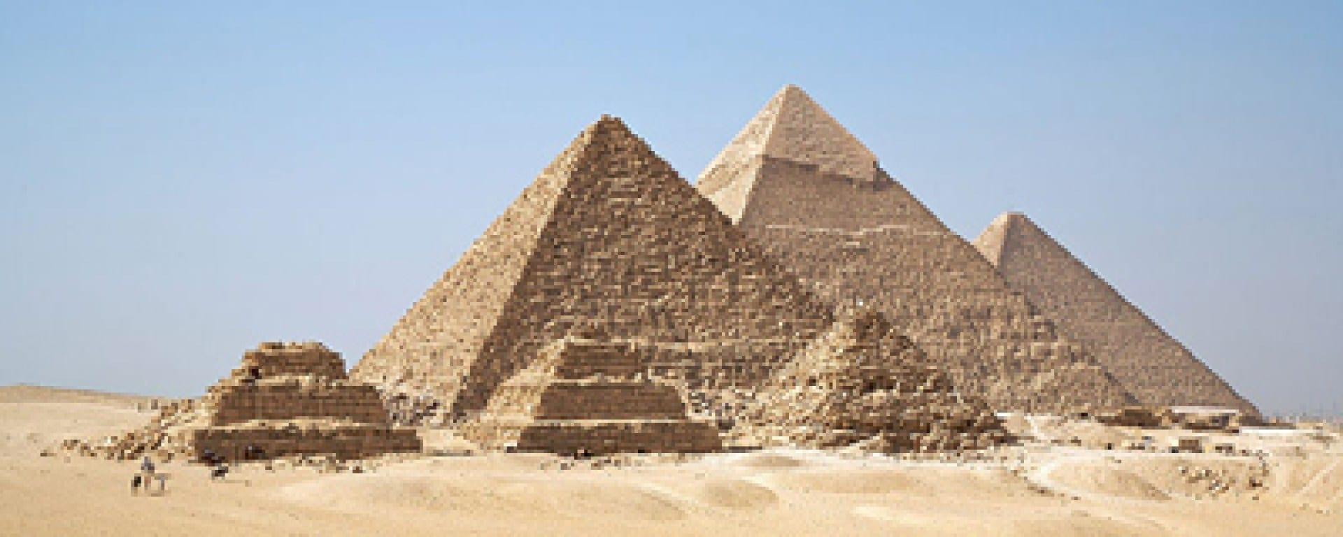 yan yana üç adet taş yapı ve arkada yan yana üç adet piramit