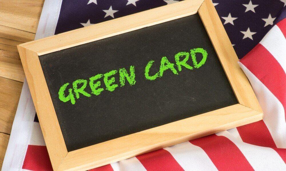 amerikan bayrağı üzerinde tablo şeklinde bir kara tahta tahtanın üzerinde green card yazısı.