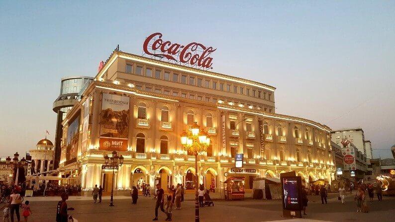 sokak lambalarıyla aydınlatılan kalabalık bir şehir meydanı ve şehir meydanında bulunan ışıklarla aydınlatılmış bir bina. Işıklı olan binan üzerinde coca cola logosu.